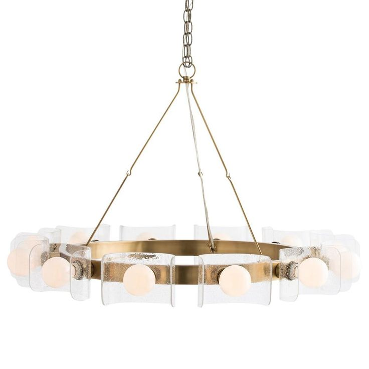 """The antique brass ring is held by dainty metal rods that hook together then meet at the chain at the top. Twelve lights are secured to the outside of the brass ring through the curved seedy glass semi-shields. The perfect size over a large round table. Shown with frosted globe bulbs.  25-34.5""""H x 38""""D Seedyglass Steel with brass finish Uses (12) 40Watt A19 Incandescent Bulbs Approved for use in covered outdoor areas     IN STOCK & READY TO SHIPPurchase now to ensur..."""