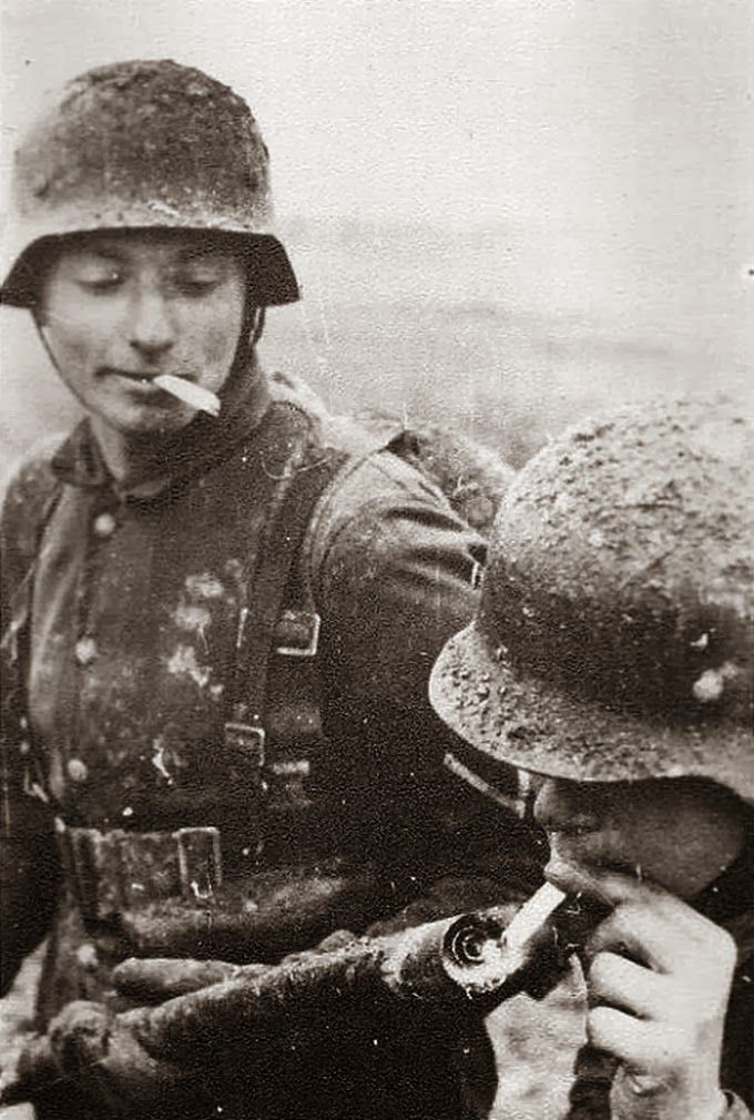 A German soldier lights his cigarette with a flame thrower, circa 1941
