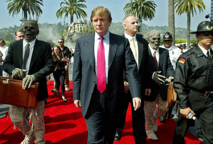 """Donald Trump, center, arrives at Universal Studios Hollywood and is accompanied by persons dressed as mummies in business attire Friday, July 9, 2004, in the Universal City section of Los Angeles. Trump is casting for """"The Apprentice"""" television show's the third season. (AP Photo/Ric Francis)"""