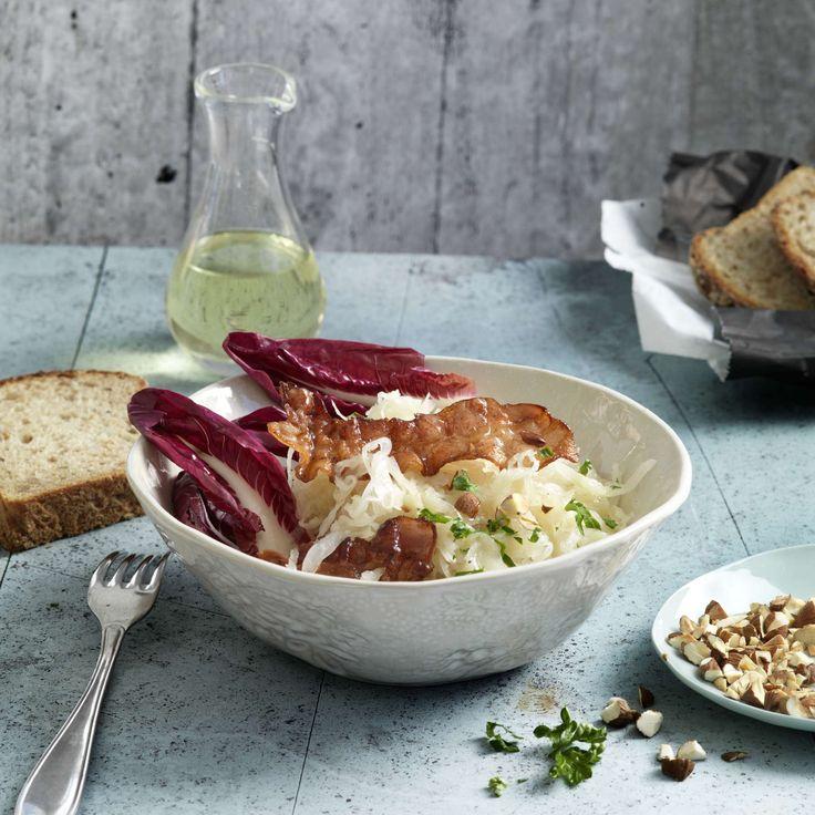 Sauerkrautsalat mit Speck. Statt warm wird das Sauerkraut als Salat an Honigdressing zubereitet, mit knusprigen Specktranchen, gerösteten Mandeln und Cicorino rosso und Petersilie.