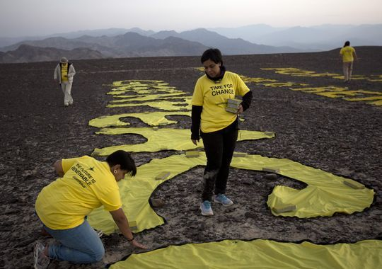 Greenpeace activists arrange the letters delivering a message in Peru