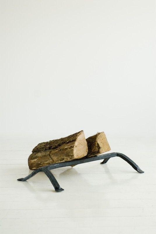 Oryginalny stojak na drewno wykonany z ręcznie kutego żelaza. Siła formy i materiału.