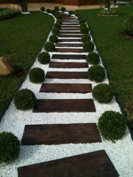 Camino de jardín con madera, gravilla blanca y boj recortado