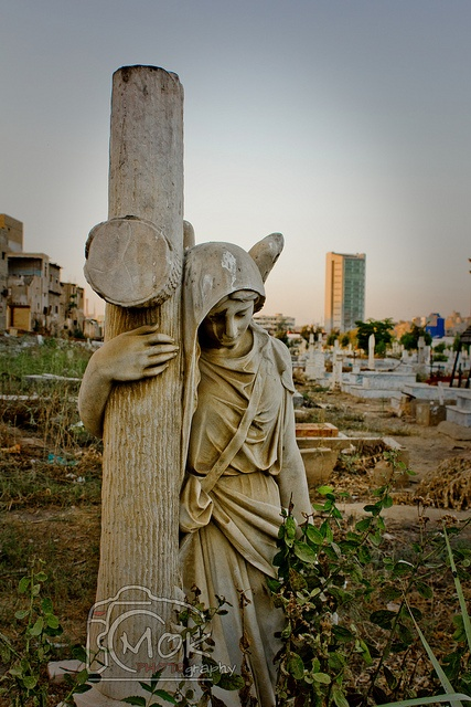 Cross headstone on grave in Christian cemetery.  The largest Graveyard of Christians in Karachi. The oldest grave stone show the sign of people buried in 18th century. Most of old graves are of Polish people who stayed in Karachi to join royal army in world war.  The city's district government in 2011 installed two new gates and paved the pathways inside the graveyard. - Pakistan!