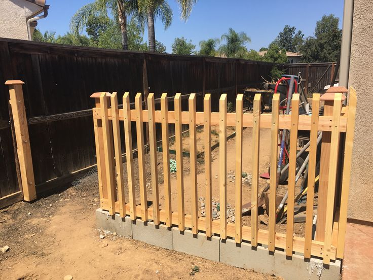 Build a fence using cinder blocks as the base. All the wood was purchased and cut to fit using a saw. Posts cemented into the cinder block. Wood is being stained and cinder blocks painted to match the patio color.