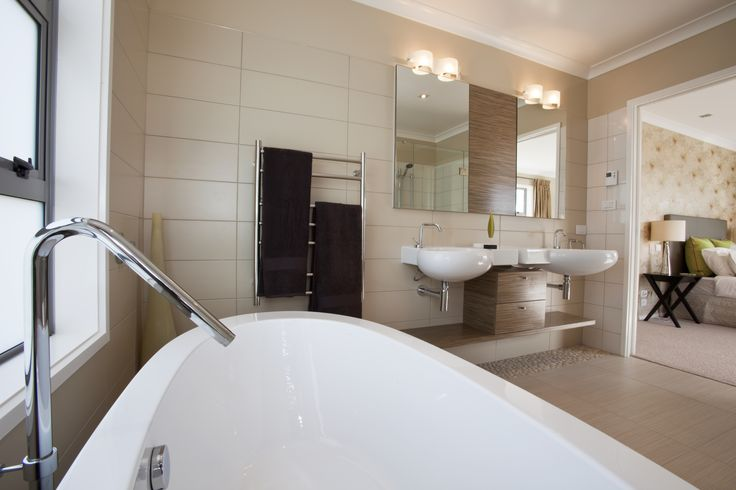 The bath is all about style, freestanding with a centre tap. The ensuite also features two wall hung basins with twin mirrors and cabinetry inbetween. While a generously sized shower sits in the other corner.