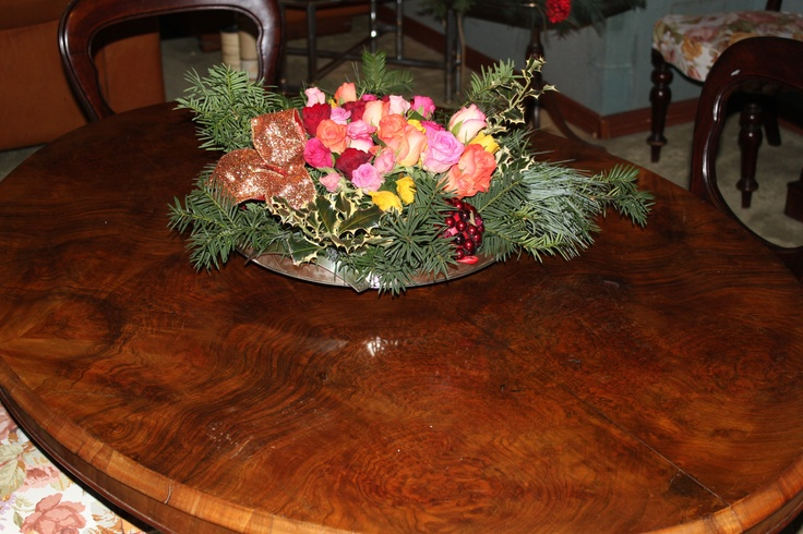 Christmas centerpiece: pine, fir, holly, roses, red glittering cones, bells of the gnomes and big blackberry lacquered papier-mâché