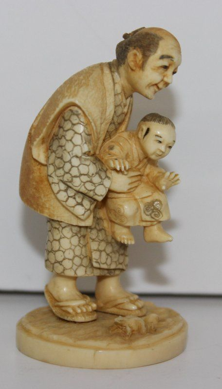 """19th C. Japanese Carved Ivory Netsuke. Finely carved and stained man with child. Signed on bottom. Measures - 2 1/4"""" high, weighs - 21.3 grams."""