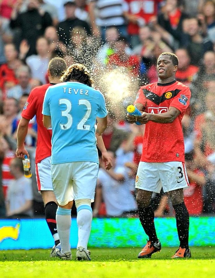 Patrice Evra squirts water over former colleague Carlos Tevez.