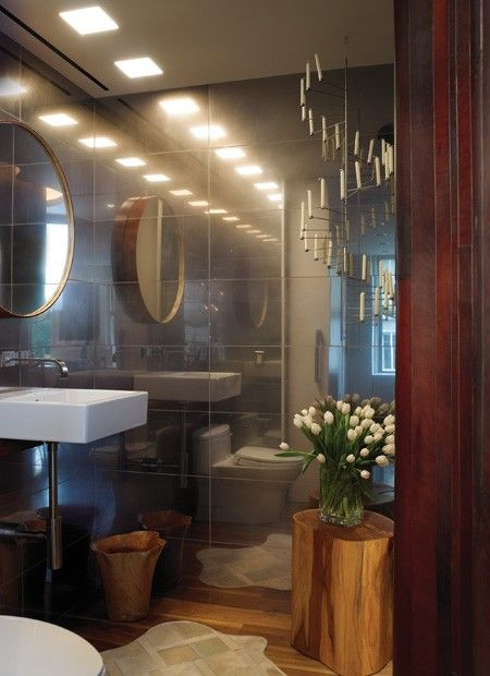 Reflective Bathroom Walls    A spiraling Scandinavian chandelier and wood accents soften this modern space.