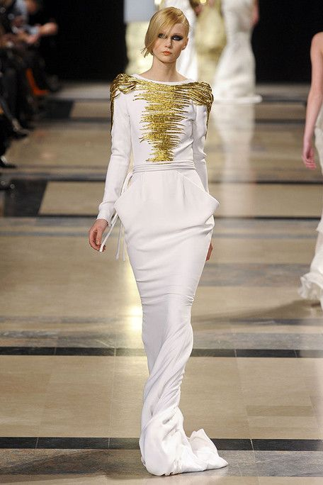 Stephane Rolland Fashion / gold and white long sleeve gown on the runway