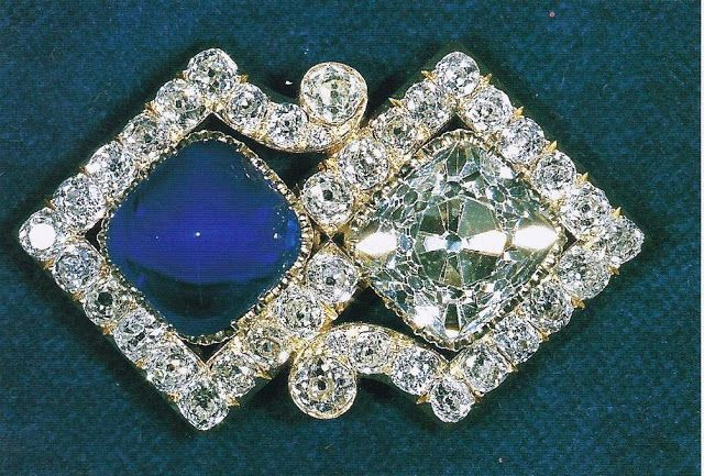 Queen Mary's Russian Brooch: Queen Alexandra's sister, the Empress Marie Feodorovna of Russia, gave Princess May of Teck this unusual brooch consisting of a large square-cut diamond and a square cabochon sapphire set in a scroll frame of round diamonds as a wedding present in 1893. The Empress and her husband, Tsar Alexander III, later added sapphire and diamond bracelets to the gift.