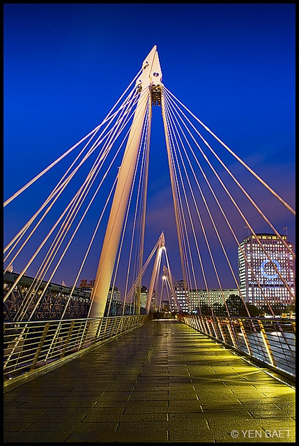 The Hungerford Bridge crosses the River Thames in London, and lies between Waterloo Bridge and Westminster Bridge. It is a steel truss railway bridge—sometimes known as the Charing Cross Bridge—flanked by two more recent, cable-stayed, pedestrian bridges that share the railway bridge's foundation piers, and which are named the Golden Jubilee Bridges.