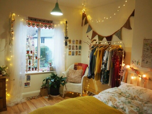 Eclectic, bohemian and cosy bedroom with fairy lights, bunting and photos on the wall. Love the clothes rail