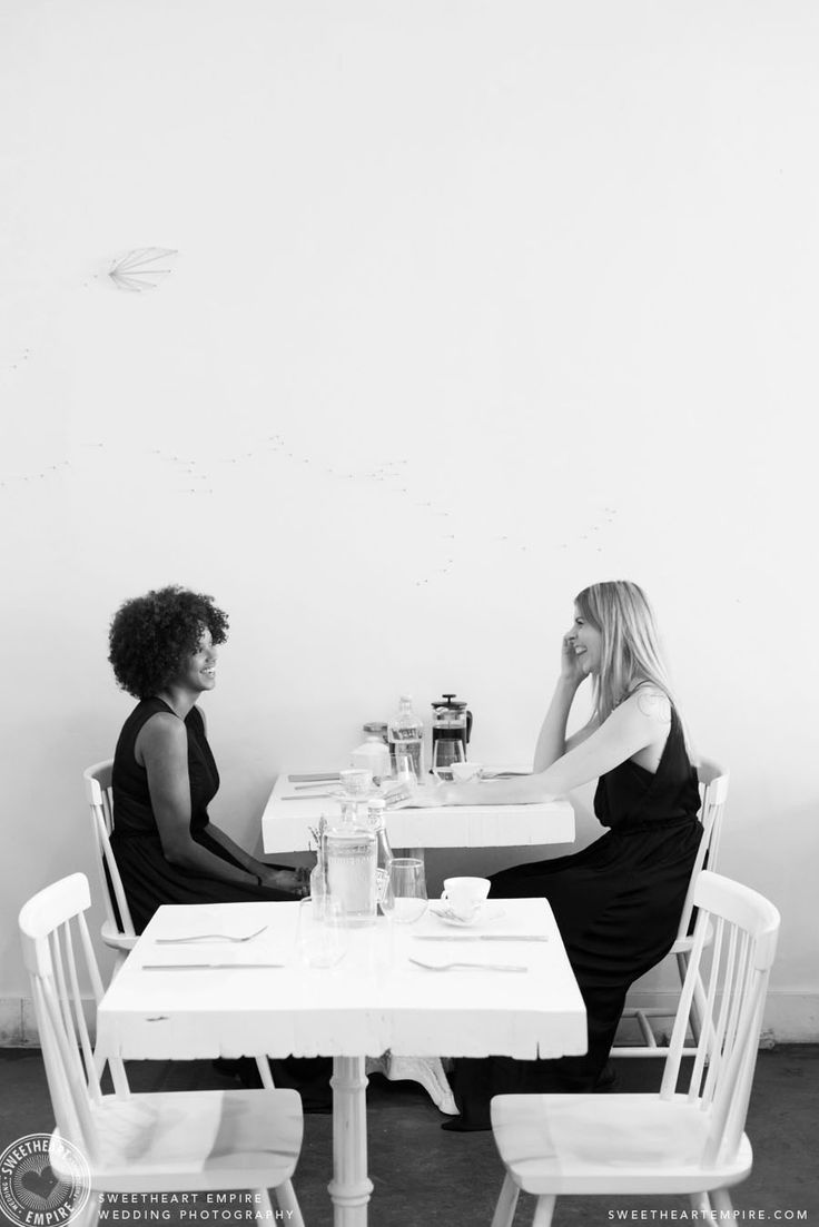 Two brides-to-be laughing over brunch. Brunch engagement photos, L'Ouvrier Kitchen Bar. Toronto Engagement photos, same-sex wedding, restaurant engagement session. #sweetheartempire #sweetheartempirephotography