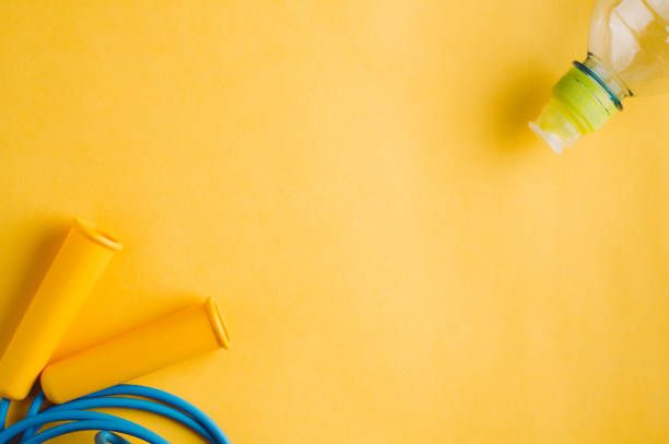 water bottle and skipping rope on a yellow background