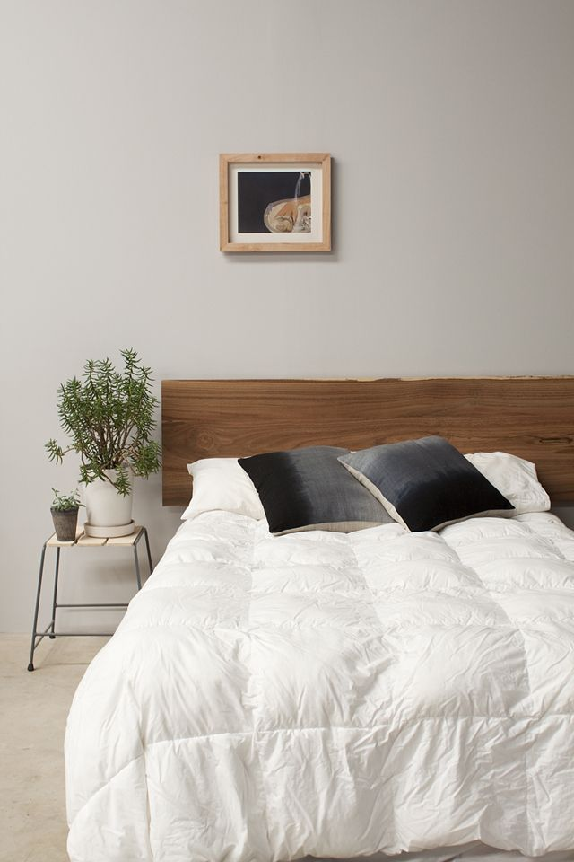 A gorgeous one off bed head made from a slab of timber sourced at the local sawmill. Photo: Maker Studio // timber frame; indoor plant; stool as bedside table; white quilt; ombre cushion