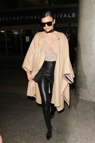 12 chic winter outfit ideas to inspire your look this season: Miranda Kerr in a camel cape, leather leggings and boots.