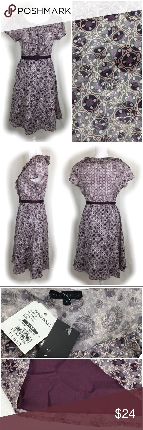 """NWT Paperdolls Purple Print Cotton Dress NWT Paperdolls Purple Print Cotton Dress.  Size XL.  Lightweight purple cotton print fabric with complementing floral embroidery.  Removable purple satin belt.  Purple satin button-down front bodice.  Ruffle neckline.  Cap sleeves.  Lined skirt.  Side zipper closure.  100% cotton with polyester lining.  Hand or machine wash cold, tumble dry low.  Length shoulder to hem 40"""".  Pit to pit: 20"""".  Waist: 18"""" across.  Hips: 22"""" across.  Bottom of dress: 34""""…"""
