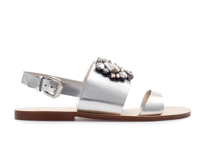 Sandalias planas plateadas con detalle floral en la parte delantera, de Zara.