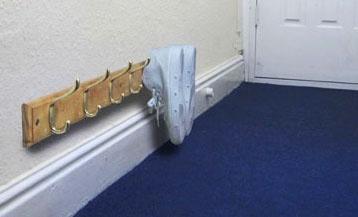 Una buenísima idea: los ganchos para pared, más abajo, son útiles ordenadores de zapatos.