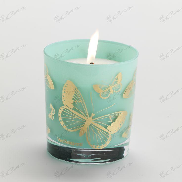 Contenitore in cristallo color verde acqua con candela e farfalle dorate sullo sfondo- Collezione Infinity