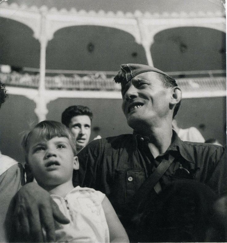 Gerda Taro © International Center of Photography Republican militiaman and child at bullfight and military show, Barcelona, August 1936