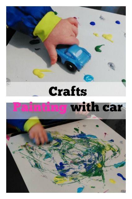 De baby kan met een auto daar de verf rijden die op het doek licht.