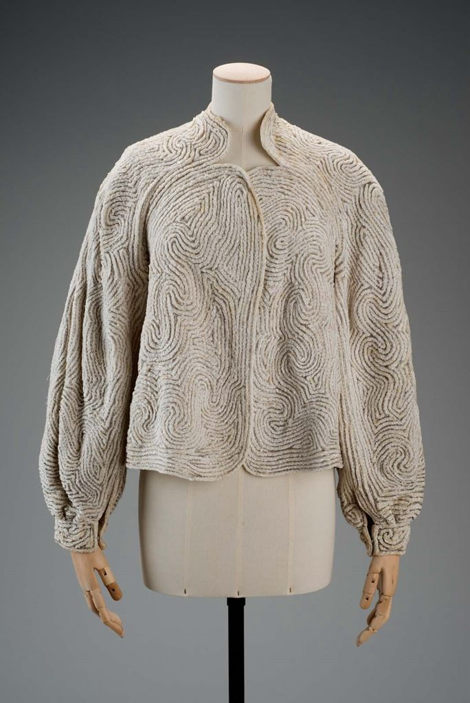 Jacket   Designed by Roy Halston Frowick, known as Halston (American, 1932-1990)   United States, 1980's   Material: silk   Cream colored jacket with scalloped collar, no front closures, and button-closure cuffs. Swirling design made of sewn-on silver beads   Museum of Fine Arts, Boston