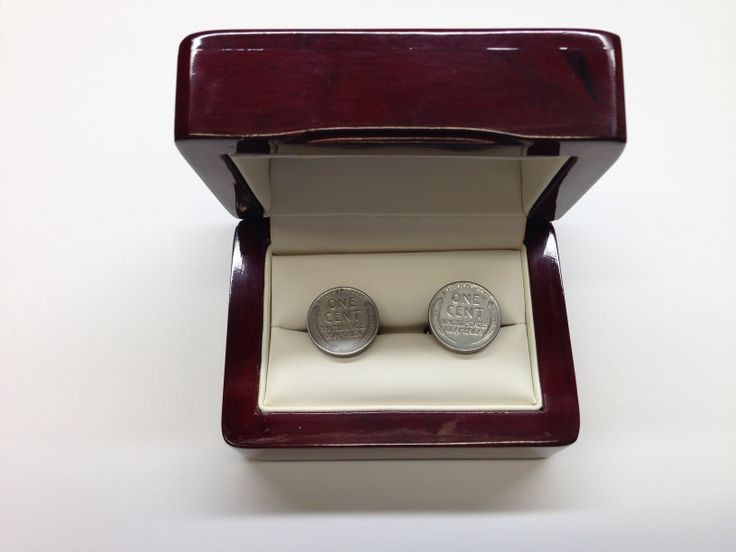 Steel penny cufflinks in the fancy box. These were cast during WWII because of the copper rationing.  The steel cent is the only regular-issue United States coin that can be picked up with a magnet. The steel cent was the only coin issued by the United States for circulation that does not contain any copper, and is actually magnetic!