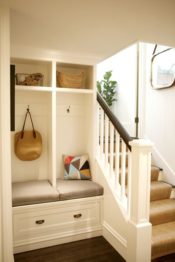 Mini mudroom built at the base of stairs is an ideal place to take off shoes and store outdoor gear. | Belathee Photography