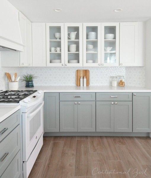 """Fotografía de Cocina renovada en tonos blancos    Esta cocina sufrió cambios en el piso, muros y muebles. El almacenaje era una prioridad para sus propietarios, pero el mobiliario anterior era """"fome"""", por lo que se buscó dar un giro de 360º en la cocina. Por ello, los muebles inferiores en tono gris azulado fueron un acierto junto a los demás elementos renovados: el piso de madera y los módulos superiores en color blanco. Una combinación magistral para hacer de la cocina un lugar nu..."""