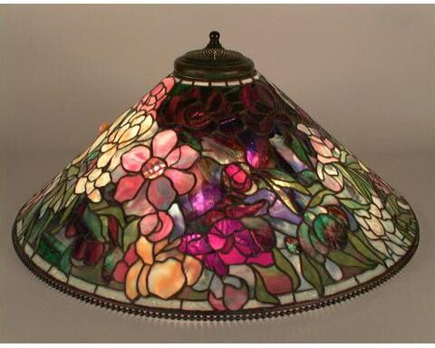 """ca. 1900-1906 ARTIST/MAKER:Tiffany Studios . (73.7 × 30.5 cm) DESCRIPTION Leaded glass and bronze Peony hanging lamp; 28"""" diameter cone-shaped shade depicting bouquet of flowers using highly textured glass and thick chunks of colored glass for the flower centers; flower colors include red, yellow, white and pink using undulating, rippled, and fibrillated glass; borders of grayish blue glass around aperture and lower rim; metal beading at top and bottom of shade."""