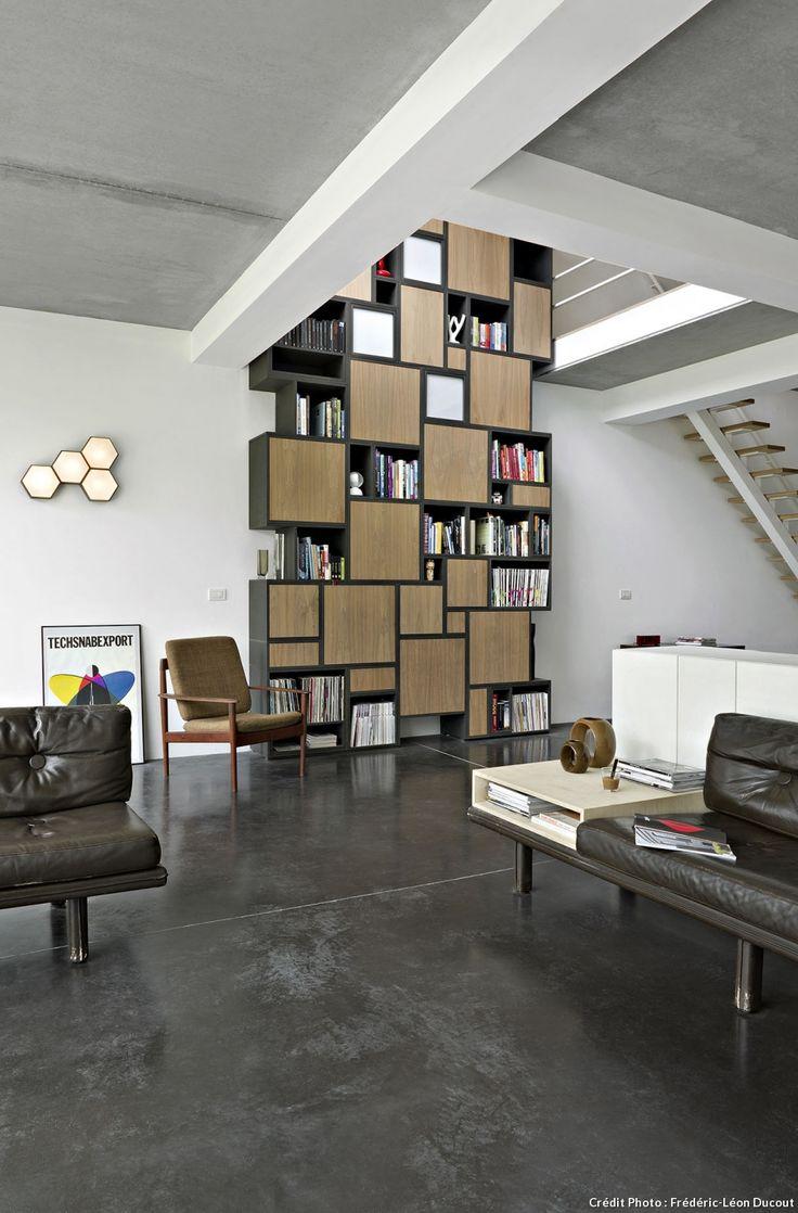 Salon avec une grande bibliothèque cube en noyer, verre sablé et medium qui se déploie jusqu'au premier étage de cette maison belge.