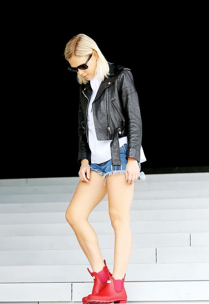Black leather moto jacket, white top, denim cutoff shorts, red rain boots, and sunglasses
