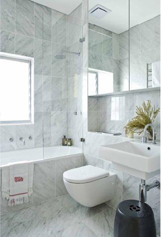Waterfall shower over bath; recessed shelf above sink; freestanding sink and hidden cistern
