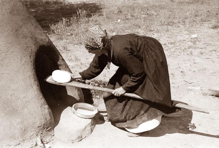 A woman baking bread in a Kiva Oven, 1939, near Taos, New ...