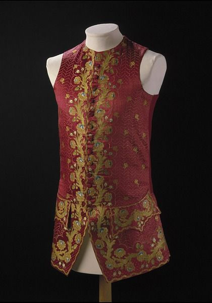 Court Waistcoat, England, Britain, 1760s, Brocaded silk. The dense covering of gold embroidery on this silk waistcoat indicates that it was worn as formal Court dress underneath a matching Frockcoat. Although very decorative to modern eyes, traditionally Court dress in Britain was more restrained than that worn elsewhere in Europe. There multi-coloured flowers and plants adorned coats and waistcoats in colourful and complicated patterns.