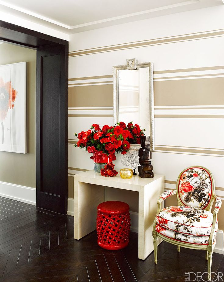 A striped accent wall, marble console table, red stool, patterned armchair, and red roses: