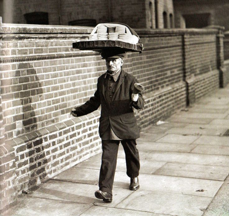 A muffin man making deliveries to households and announcing his presence with a hand bell UK, 1924.