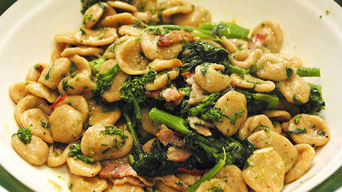 Orecchiette with broccoli rabe (orecchiette con cime di rapa) | Broccoli rabe, or rapini, is a bitter green that comes into season in autumn. It is a member of the turnip family and you will find it at selected greengrocers in bundles of large leaves with broccoli-like flower heads opening into small yellow flowers.Guy learnt this recipe from his father, Pietro, who is from Puglia in southern Italy. It's earthy and rustic – a peasant-style dish to get you through the day.