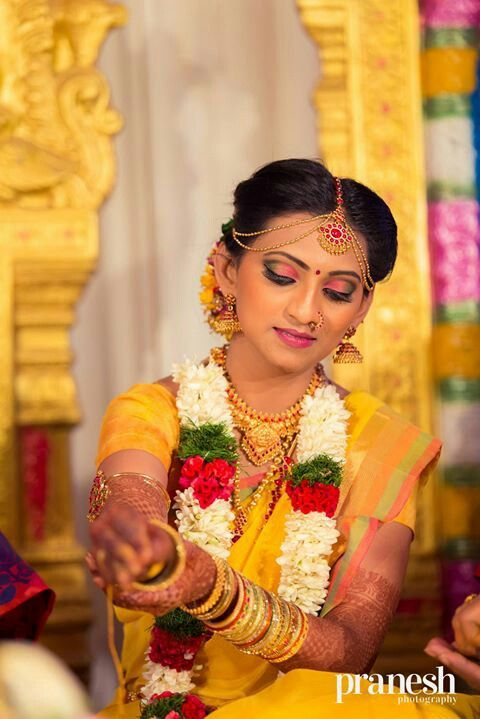 South Indian bride. Hindu bride. Yellow silk kanchipuram sari. Jhumi. Gold Jewelry. Fresh flowers in hair. Flower garland.