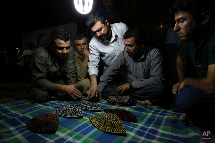 In this Tuesday, July 7, 2015 photo, Kurdish men discuss which hat to pick up while playing a game of Klawane in Irbil, Iraq. The traditional Iraqi Kurdish game is only played after Iftar during Ramadan. Two teams of four compete, where one team hides a ring in a traditional hat. The other team has to guess in which hat the ring is hidden. The team that hides the ring scores points for each hat that is leftover after the other team finds the ring. (AP Photo/Bram Janssen)