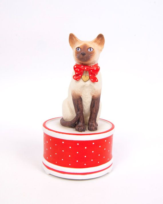 This is a beautiful Siamese Cat Music Box by Schmid in excellent condition with no chips or cracks. Description from etsy.com. I searched for this on bing.com/images