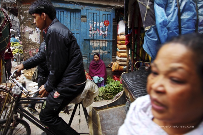 Rickshaw driver and vegetable seller in the busy street of Kathmandu