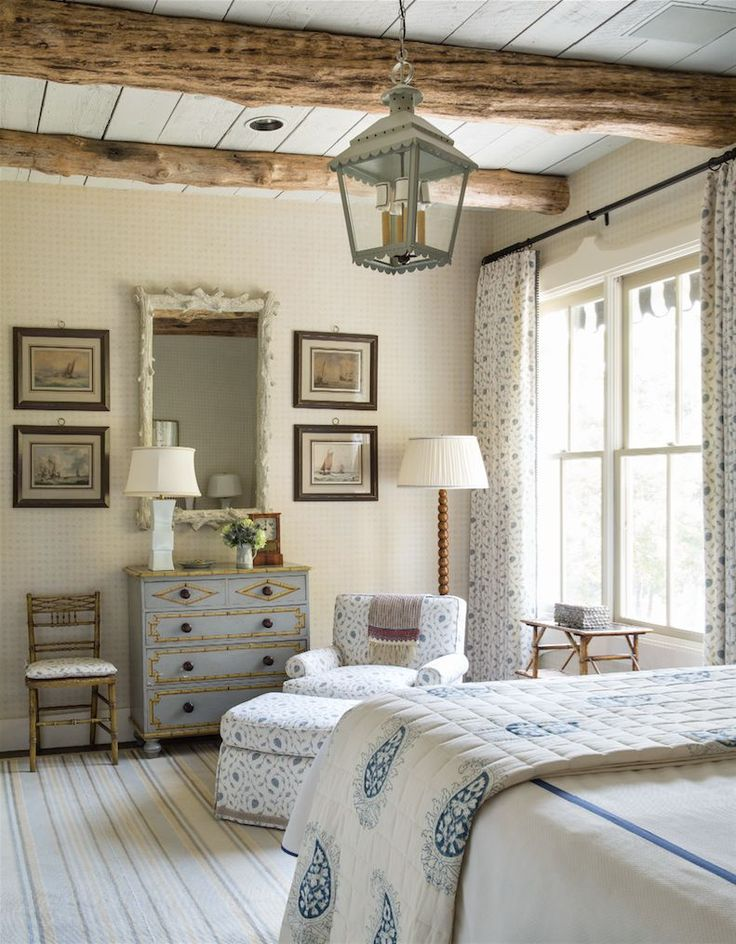 Airy country cottage bedroom style with white-washed floors, blue and white bedding, a patterned lounge chair and matching curtains, exposed beams and a vintage French dresser.