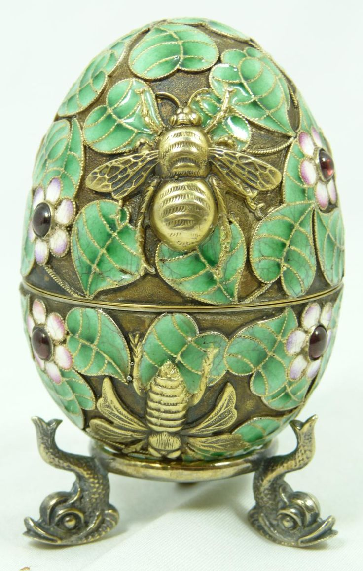 Fine Decorative Arts Russian Silver Enameled Egg BoxHaving Floral Design Throughout with Raised Gold Wash Flies and Bees. Has 8 Cabochon Cut Rubies Set Throughout. Gold Wash Interior. Set on Three Fish Feet. Measures 3 Inches in Height + 3/8 Inches Base Height
