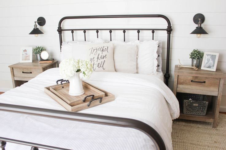 A farmhouse inspired master bedroom with industrial elements, featuring Raymour & Flanigan furniture