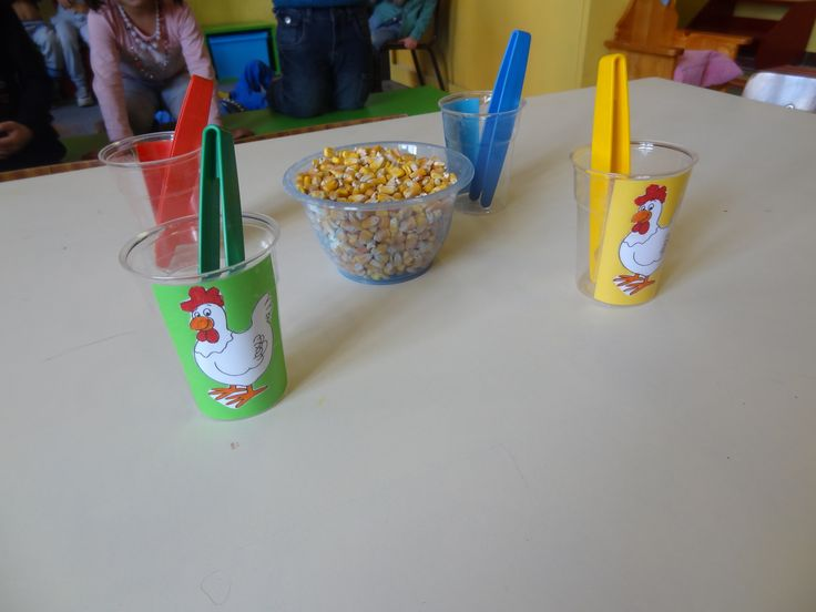 Fine motor game using tweezers to pick up corn kernels and carry to a cup.