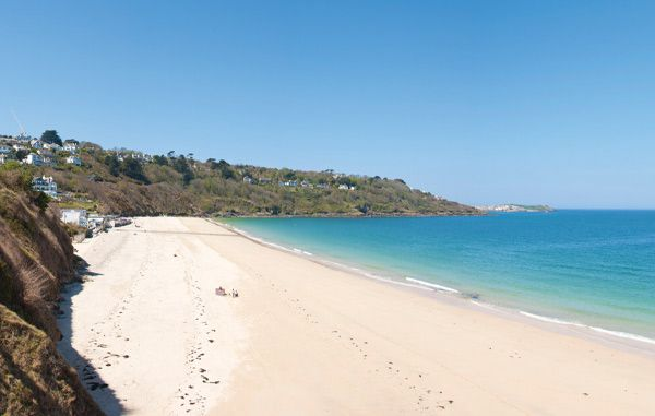 Carbis Bay Beach, located on the approach to St Ives, Cornwall is a tranquil cove, with white sand, clear water and surrounded by lush greenery.
